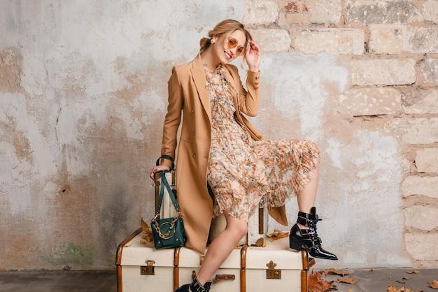 Attraktive stilvolle blonde frau im beigen mantel, der auf koffern gegen wand in der straße sitzt