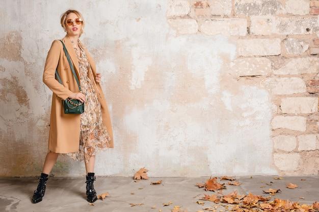 Attraktive stilvolle blonde frau im beigen mantel, der gegen weinlesewand aufwirft