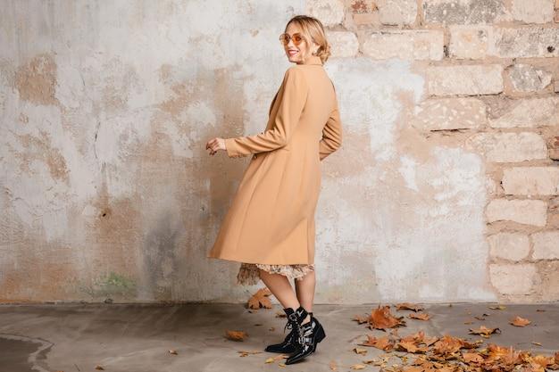 Attraktive stilvolle blonde frau im beigen mantel, der in straße gegen weinlesewand geht