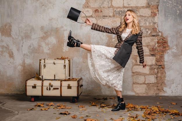 Attraktive stilvolle blonde frau in der karierten jacke, die gegen wand in der straße geht