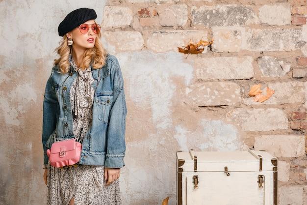 Attraktive stilvolle blonde frau in jeans und übergroße jacke, die gegen wand in der straße aufwirft