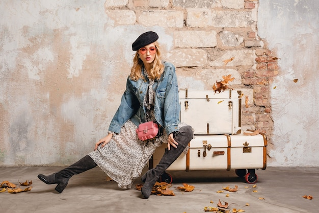 Attraktive stilvolle blonde frau in jeans und übergroße jacke, die gegen wand in der straße geht