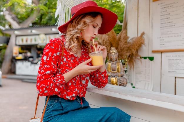 Attraktive stilvolle blonde lächelnde frau im strohroten hut und im sommermode-outfit der bluse, die natürlichen fruchtcocktail-smoothie trinkt