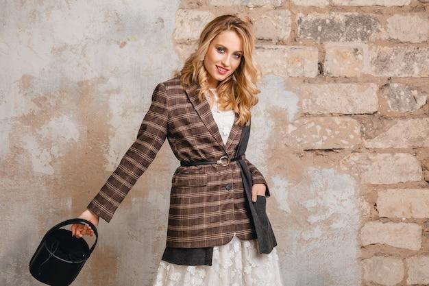 Attraktive stilvolle blonde lächelnde frau in karierter jacke gegen wand in der straße