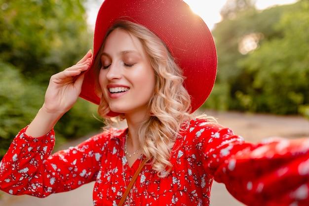 Attraktive stilvolle blonde lächelnde frau in strohrotem hut und bluse sommermode-outfit, das selfie-foto macht