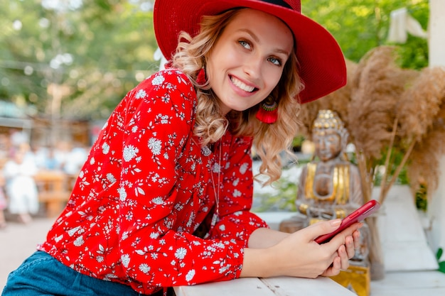 Attraktive stilvolle blonde lächelnde frau in strohrotem hut und bluse sommermode-outfit, das unter verwendung des smartphone-cafés hält