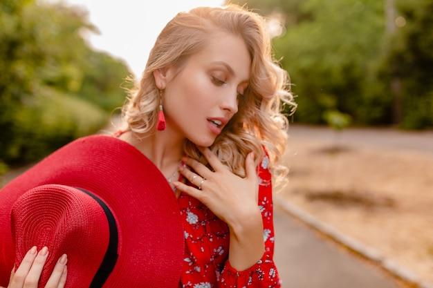 Attraktive stilvolle blonde lächelnde frau in strohrotem hut und bluse sommermode-outfit sinnlich