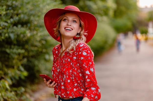 Attraktive stilvolle blonde lächelnde frau in strohrotem hut und bluse sommermode-outfit unter verwendung des telefons