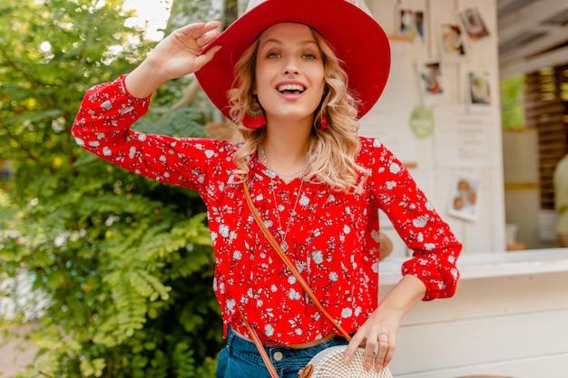 Attraktive stilvolle blonde lächelnde frau in strohrotem hut und bluse sommermode-outfit