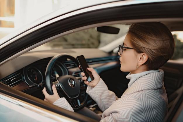 Attraktive stilvolle frau, die im auto sitzt, gekleidet in mantelwinterstil und brille mit smartphone