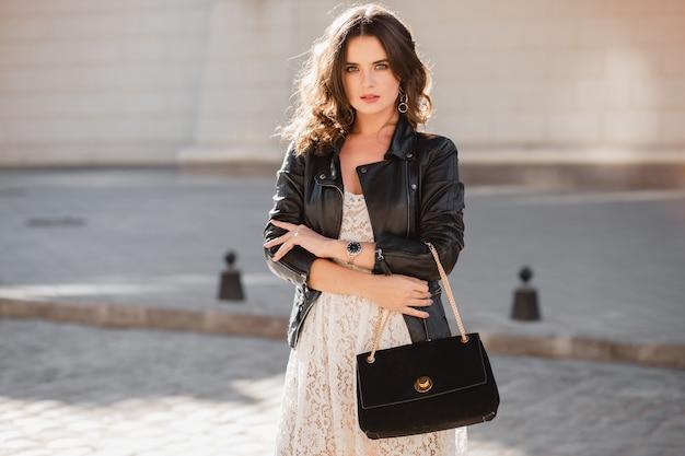 Attraktive stilvolle frau, die in der straße im modischen outfit geht, geldbörse hält, schwarze lederjacke und weißes spitzenkleid trägt, frühlingsherbststil