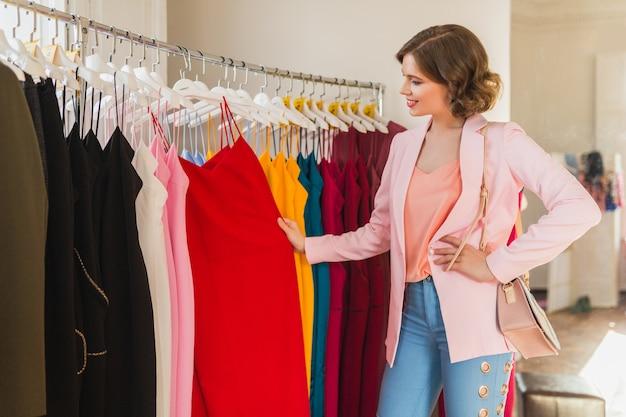 Attraktive stilvolle frau, die kleidung im bekleidungsgeschäft wählt