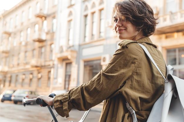 Attraktive stilvolle frau, die mantel trägt ein fahrrad auf einer stadtstraße reitet