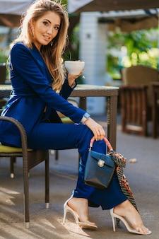 Attraktive stilvolle frau gekleidet im blauen eleganten anzug, der am tisch im kaffeetrinkbecher des cappuccino sitzt