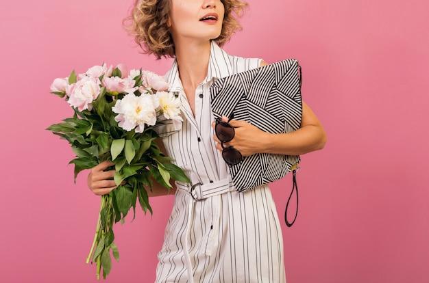 Attraktive stilvolle frau im eleganten weißen gestreiften kleid, das handtasche und blumenstrauß hält