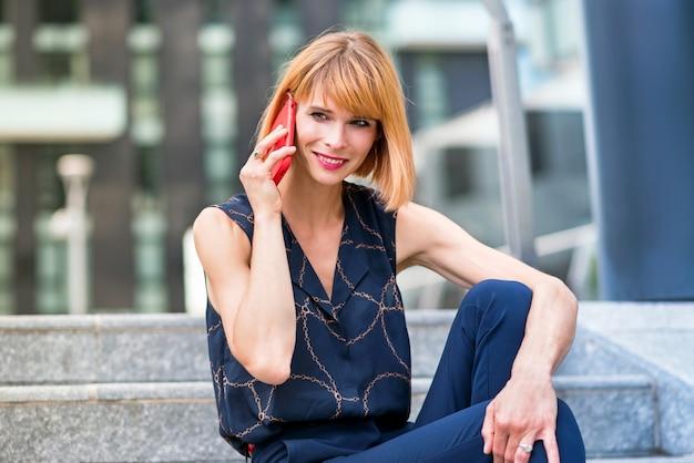 Attraktive, stilvolle geschäftsfrau, die lächelt, während sie auf einem mobiltelefon chattet, während sie sich auf außentreppen in der stadt entspannt, in einer nahaufnahme von ihr, die dem gespräch zuhört