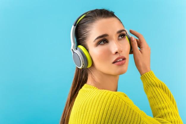 Attraktive stilvolle junge frau, die musik in den kabellosen kopfhörern hört, die glücklich tragen, gelbe strickpullover bunte art und weise zu tragen, die lokal auf blauer wand aufwirft