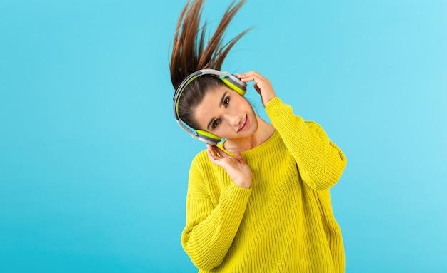 Attraktive stilvolle junge frau, die musik in den kabellosen kopfhörern hört, die glücklich tragen, gelbe strickpullover bunte artmode posieren, die auf blauem hintergrund lokalisiert wird, der langen haarschwanz winkt