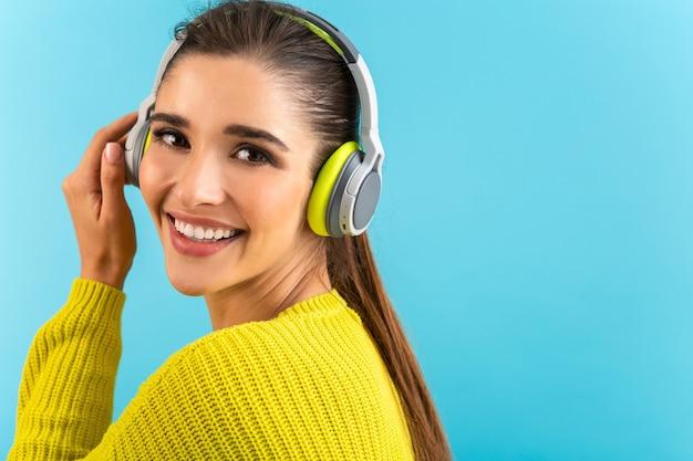 Attraktive stilvolle junge frau, die musik in den kabellosen kopfhörern hört, die glücklich tragen, gelben strickpullover bunte artmode, die lokal auf blauem hintergrund aufwirft