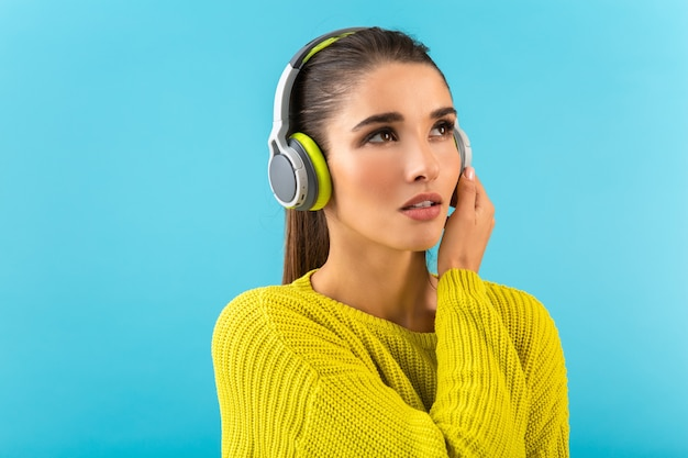 Attraktive, stilvolle junge frau, die musik in drahtlosen kopfhörern hört, die gerne gelbe strickpullover im bunten stil trägt