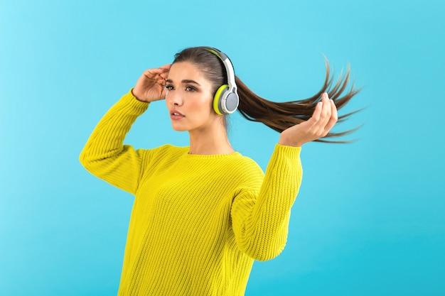 Attraktive, stilvolle junge frau, die musik in drahtlosen kopfhörern hört und einen gelben strickpullover trägt
