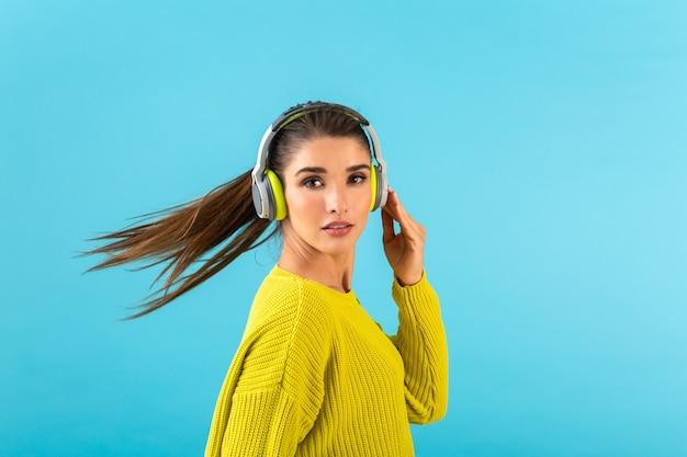 Attraktive stilvolle junge frau, die musik in kabellosen kopfhörern hört, die glücklich gelben strickpullover tragen