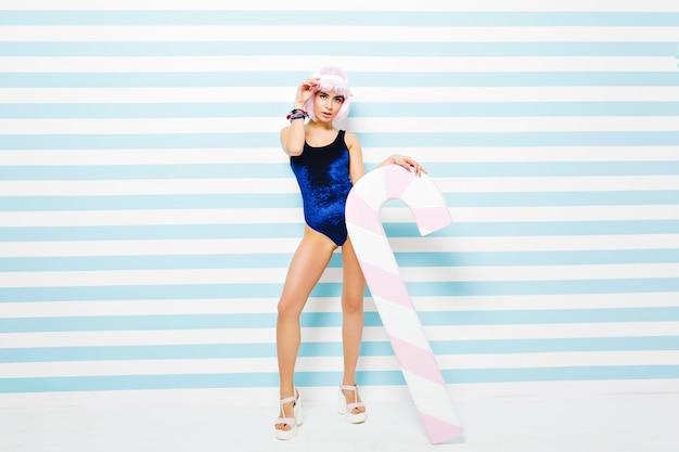 Attraktive stilvolle junge frau im body, der sich auf blau-weiß gestreifter wand entspannt. tragen geschnittene rosa frisur, absätze, strandmütze. sexy model, großer lutscher, schauend.