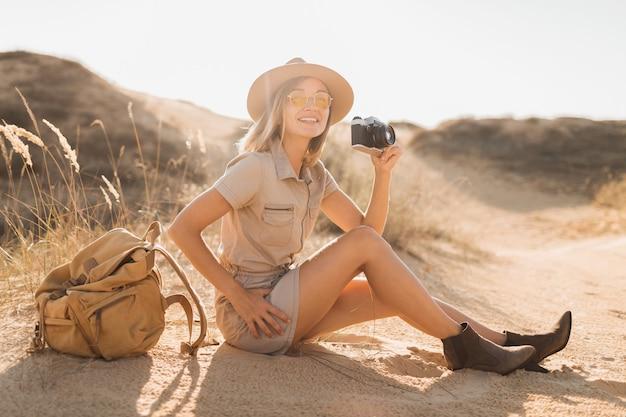 Attraktive stilvolle junge frau im khaki-kleid in der wüste, die in afrika auf safari reist, hut und rucksack trägt und foto auf vintage-kamera macht
