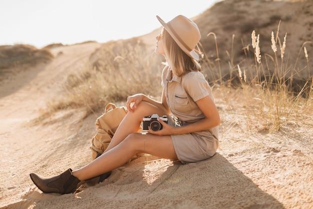 Attraktive stilvolle junge frau im khakikleid in der wüste, die in afrika auf safari reist, hut und rucksack tragend