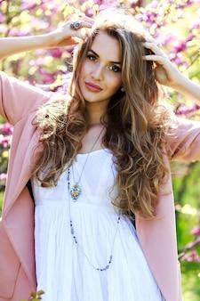 Attraktive stilvolle junge frau in hellweißem kleid, rosa mantel, mit langen haaren, die im garten mit blühender sakura gehen