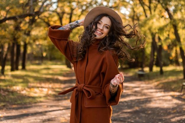 Attraktive stilvolle lächelnde dünne frau mit dem lockigen haar, das im park geht, gekleidet in warmem braunem mantel, herbsttrendiger modischer straßenstil