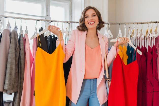 Attraktive stilvolle lächelnde frau, die kleidung im bekleidungsgeschäft wählt