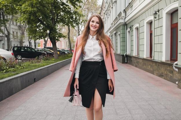 Attraktive stilvolle lächelnde frau, die stadtstraße im rosa mantelfrühlingsmodetrend, eleganter stil geht