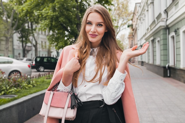 Attraktive stilvolle lächelnde frau, die stadtstraße im rosa mantelfrühlingsmodetrend hält geldbörse, eleganter stil
