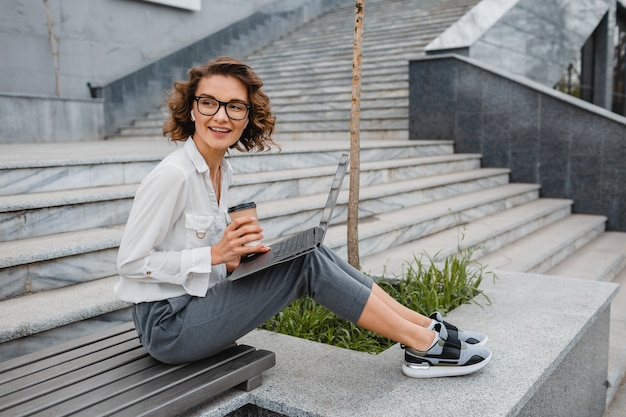 Attraktive stilvolle lächelnde frau mit brille, die am laptop schreibt