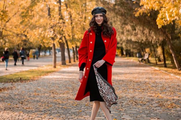 Attraktive stilvolle lächelnde frau mit dem lockigen haar, das im park geht, gekleidet im warmen roten mantel herbst trendige mode, straßenart, tragenden baskenmützenhut und schal mit leopardenmuster