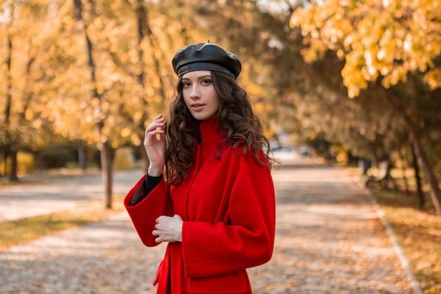Attraktive stilvolle lächelnde frau mit dem lockigen haar, das im park geht, gekleidet im warmen roten mantel herbstliche modische mode, straßenart, baskenmützenhut tragend