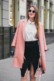 Attraktive stilvolle lächelnde reiche frau, die stadtstraße im rosa mantel geht