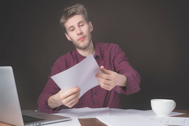 Attraktive studentenarbeit mit papier und laptop und kaffeetrinken auf dunklem hintergrund b