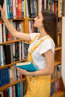 Attraktive studentin, die buch in der bibliothek wählt