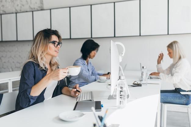 Attraktive studentin mit blonden haaren, die sich auf prüfungen vorbereiten, in der nähe des computers sitzen und latte trinken