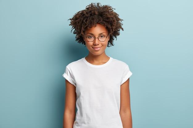 Attraktive studentin mit lockigem haar, trägt transparente brille, weißes t-shirt, steht vor blauem hintergrund, hat ruhigen gesichtsausdruck, zartes lächeln,