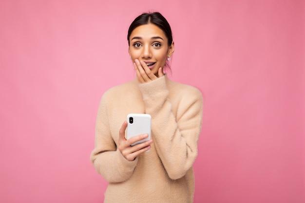 Attraktive süße junge erstaunte brunet-frau mit beige warmem pullover, die isoliert über rosafarbenem hintergrund steht und per telefon im internet surft und in die kamera schaut