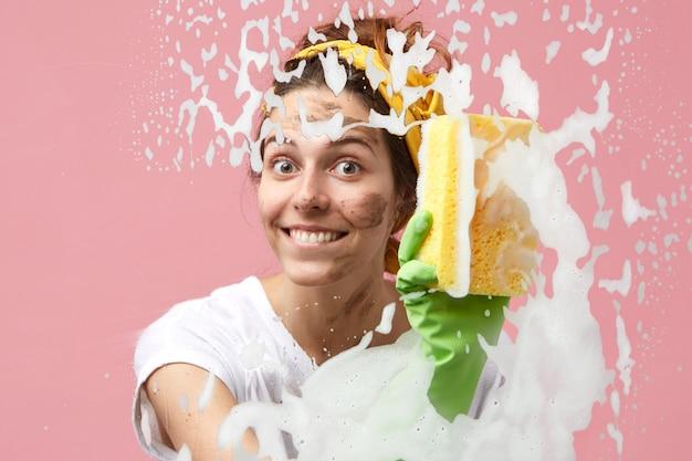 Attraktive süße junge kaukasische frau vom reinigungsdienst, die breit lächelt, während sie in der wohnung aufräumt, glasoberfläche des fensters oder der duschkabine wäscht, sich aufgeregt und glücklich über ihren job fühlt
