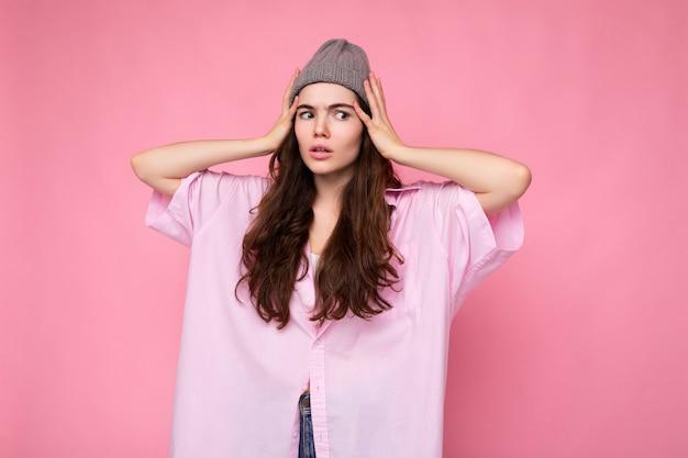 Attraktive süße nette entzückende zarte junge lockige brünette frau, die rosa hemd und grauen hut trägt