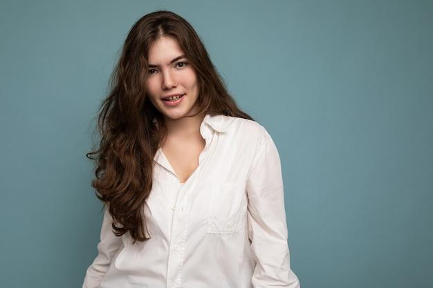 Attraktive süße nette entzückende zarte junge lockige brünette frau, die weißes hemd einzeln auf blau trägt