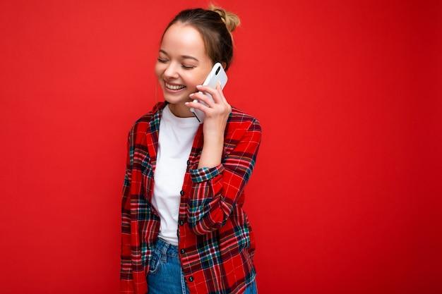 Attraktive süße positive junge blonde frau, die isoliert über roter wand steht und ein lässiges rotes hemd und ein weißes t-shirt trägt, das auf dem handy spricht und zur seite schaut.