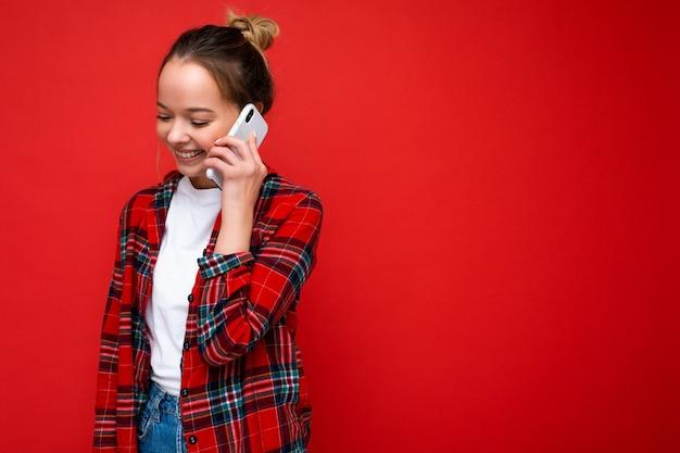 Attraktive süße positive junge blonde frau, die isoliert über roter wand steht und ein lässiges rotes hemd und ein weißes t-shirt trägt und auf dem handy nach unten spricht