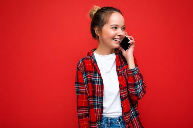 Attraktive süße positive lächelnde junge blonde frau, die isoliert über rot steht