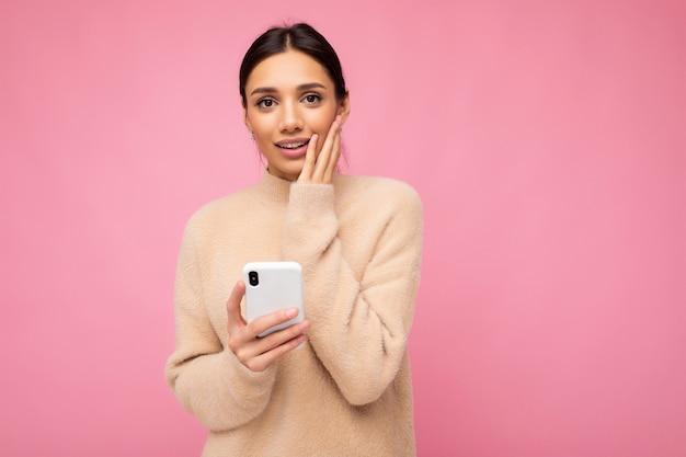 Attraktive süße traurige junge brunet-frau, die beige warmen pullover trägt, die einzeln auf rosafarbenem hintergrund steht und per telefon im internet surft, die kamera anschaut und besorgt ist.